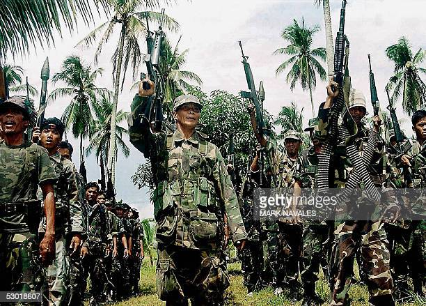 Members of the Moro Islamic Liberation Front guerrilla parade during a press conference, 04 June 2005 at Camp Darapanan, on the southern Philippine...