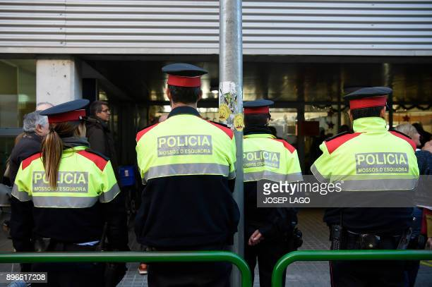 Members of the Mossos d'Esquadra stand guard outside a polling station in Sabadell on December 21 2017 during the Catalan regional election Catalans...