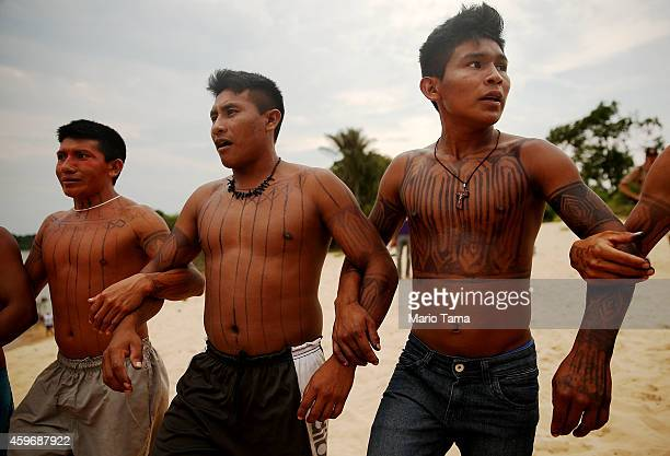 Members of the Munduruku indigenous tribe dance along the Tapajos River during a 'Caravan of Resistance'' protest by indigenous groups and supporters...