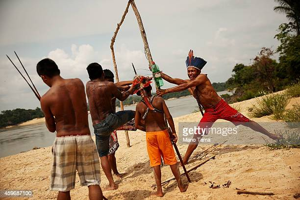Members of the Munduruku indigenous tribe try to remove an arrow shot into a bottle during target practice along the Tapajos River during a 'Caravan...