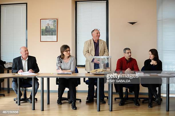 Members of the municipal council wait for voters at a polling station during the first round of the French departementales elections on March 22,...
