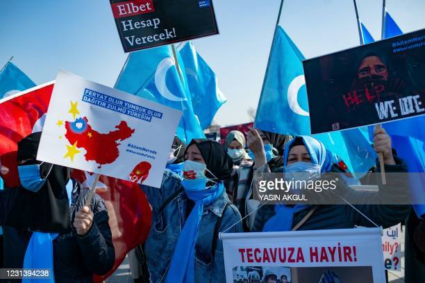 Members of the Muslim Uighur minority hold placards as they demonstrate to ask for news of their relatives and to express their concern about the...