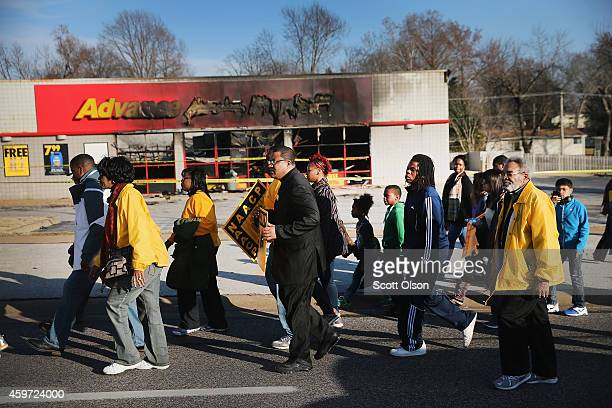 Members of the NAACP and their supporters pass by an auto parts store that was destroyed by rioters as they walk on the first day of a Journey for...