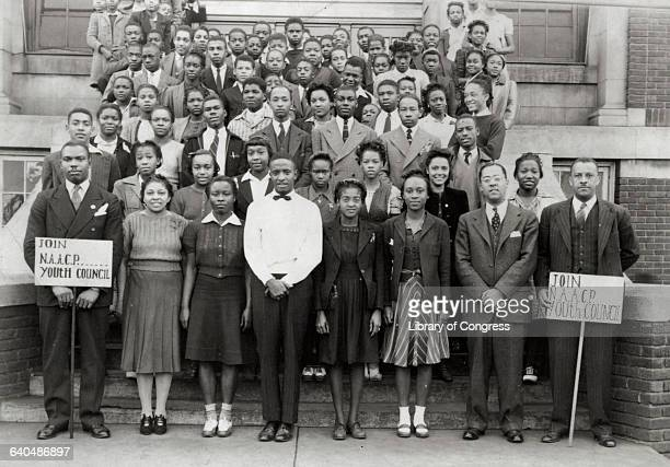 Members of the National Assoication for the Advancement of Colored People Youth Council pose on a building stairway with signs urging others to join...