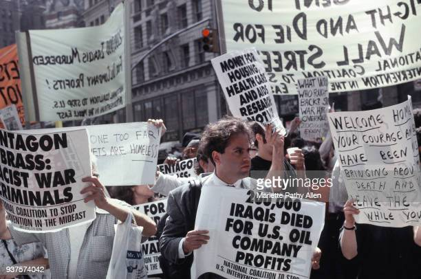 Members of the National Coalition to Stop U.S. Intervention in the Mideast carry signs and protest in a 'Say No to the War Parade' celebrating the...