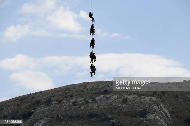 Members of the National Gendarmerie Intervention Group hang under a helicopter flying over Greolieres, southeastern France, on July 19 as they look...