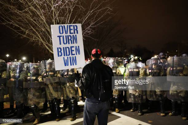 Members of the National Guard and the Washington D.C. Police keep a small group of demonstrators away from the Capital after thousands of Donald...