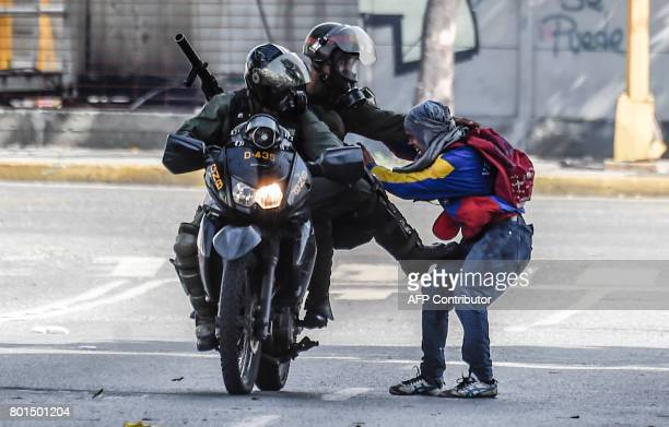 TOPSHOT Members of the National Guard arrest an opposition activist during a demonstration against the government of Venezuelan President Nicolas...