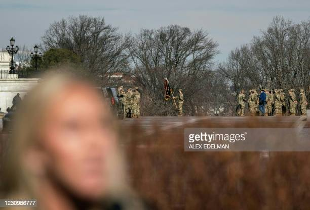 Members of the National Guard drill in the background as US Representative Marjorie Taylor Greene, Republican of Georgia, speaks during a press...