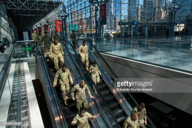 Members of the National Guard gather at the Jacob K. Javits Convention Center, which is being turned into a hospital to help fight coronavirus cases...