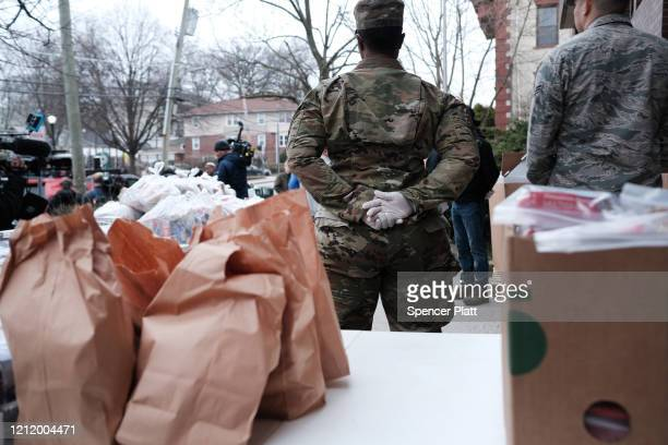 """Members of the National Guard hand out bags of food to residents near a onemile radius """"containment area"""" set up to halt the Coronavirus on March 12..."""