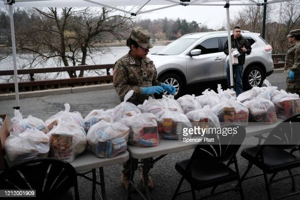 """Members of the National Guard hand out bags of food to residents of New Rochelle near a onemile radius """"containment area"""" set up to halt the..."""
