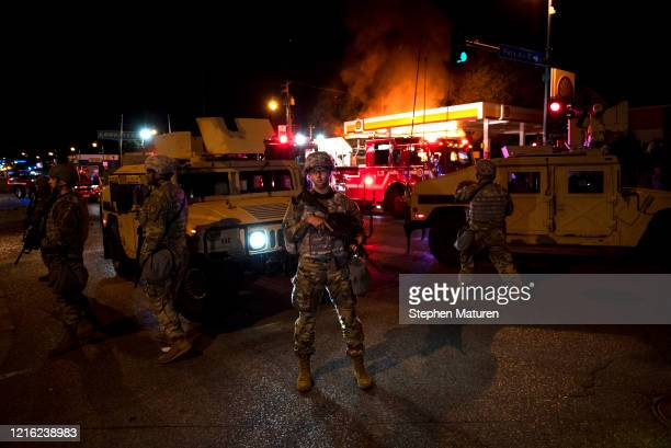 Members of the National Guard hold a perimeter as a fire crew works to put out a fire at a gas station on Lake Street on May 29 2020 in Minneapolis...