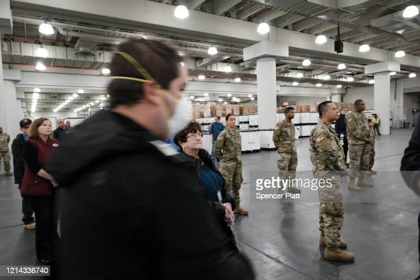 Members of the National Guard listen as New York Governor Andrew Cuomo speaks to the media at the Javits Convention Center which is being turned into...