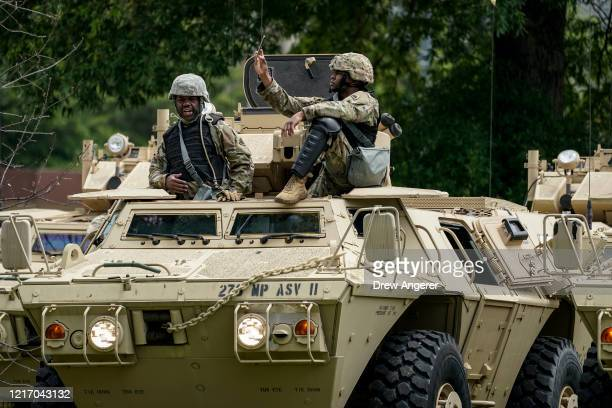 Members of the National Guard Military Police board and wait to leave for the city in armored personnel carriers at the Joint Force Headquarters of...