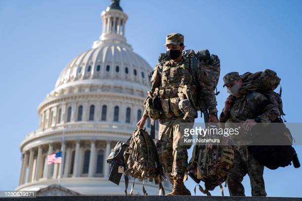 Members of the National Guard, outside the U.S. Capitol Building a day after the House of Representatives impeached President Donald Trump, and over...