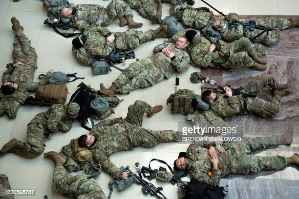 Members of the National Guard rest in the Capitol Visitors Center on Capitol Hill in Washington, DC, January 13 ahead of an expected House vote...