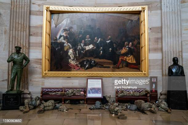 Members of the National Guard sleep in the rotunda on Capitol Hill as the House of Representativs convene to impeach President Donald Trump, nearly a...