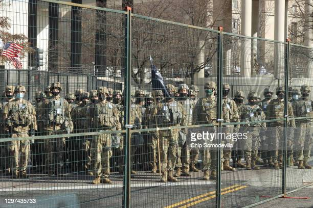 Members of the National Guard stand behind security fencing near the U.S. Capitol before the inauguration of U.S. President-elect Joe Biden and Vice...