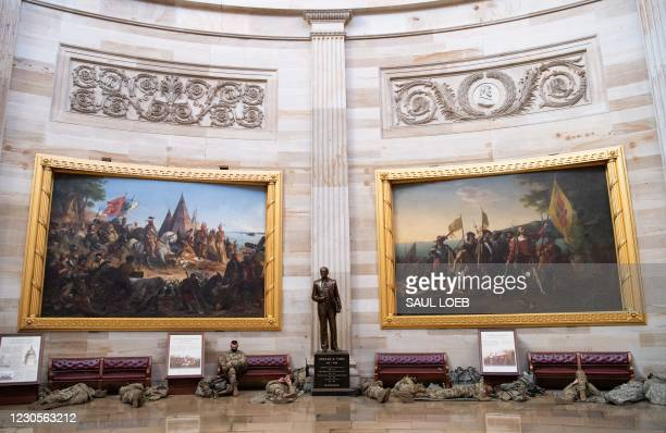 Members of the National Guard take a rest in the Rotunda of the US Capitol in Washington, DC, January 13 ahead of an expected House vote impeaching...
