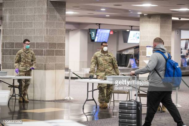 Members of the National Guard wait for arriving passengers at TF Green Airport on March 29, 2020 in Warwick, Rhode Island. Gov. Gina Raimondo...