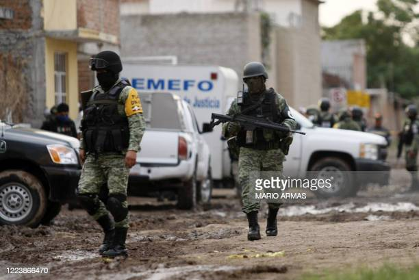 Members of the National Guard walk near the crime scene where 24 people were killed in Irapuato Guanajuato state Mexico on July 1 2020 An armed...