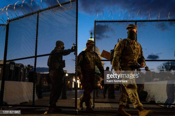 Members of the National Guard walk through a security fence surrounding the U.S. Capitol Building, which saw boosted security, Thursday, after...