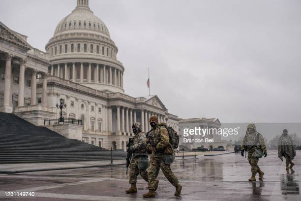 Members of the National Guard walk through U.S. Capitol grounds following the conclusion of the second impeachment trial of former President Donald...