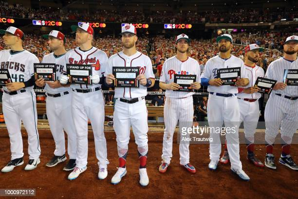 Members of the National League AllStars are seen holding up Stand Up 2 Cancer placards during the SU2C moment during the the 89th MLB AllStar Game at...