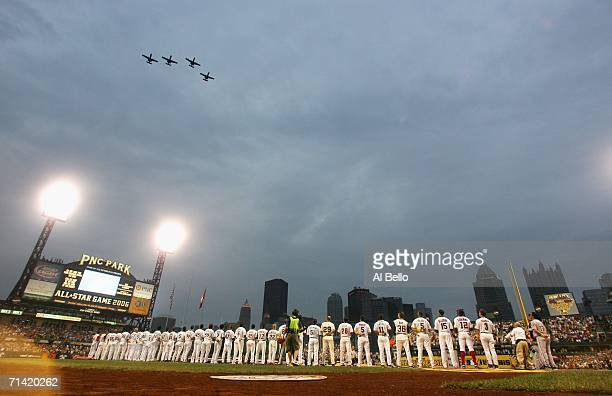 Members of the National League and American League AllStar teams line up for the National Anthem as military aircraft fly overhead before the 77th...