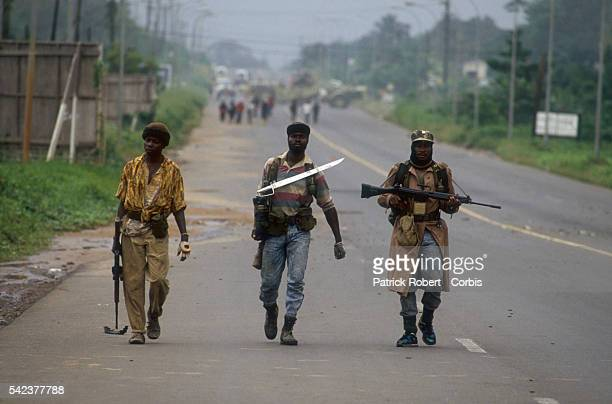 Members of the National Patriotic Front of Liberia armed with swords and assault rifles patrol the streets of Congo Town Responding to years of...