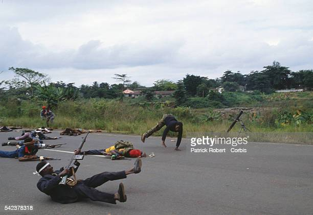 Members of the National Patriotic Front of Liberia lie in the street during a gun battle in Sinkor Responding to years of government corruption and...