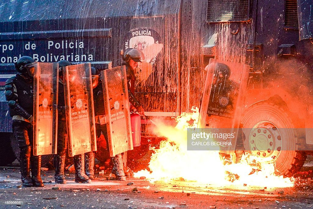 Members of the National Police clash with anti-government protesters in Caracas on April 21, 2014. Oil-rich Venezuela has been rocked by two months of deadly protests, with at least 41 people killed since a wave of demonstrations against the leftist government of Nicolas Maduro broke out in early February.