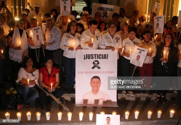 Members of the National Regeneration Movement Party lights candles during a protest following the murder of the party's mayoral candidate for the...