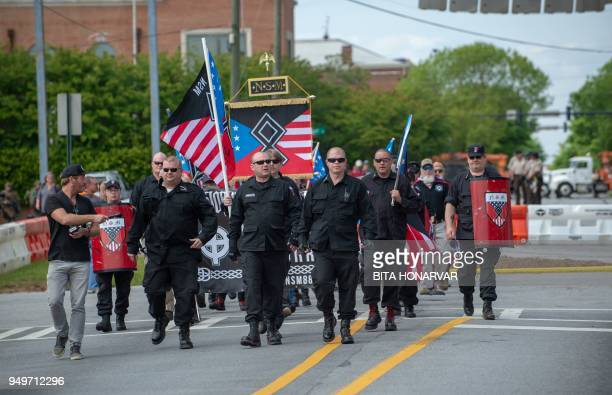 TOPSHOT Members of the National Socialist Movement and other white nationalists march toward the entrance to Greenville Street Park in Newnan Georgia...