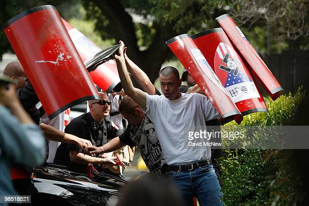 Members of the National Socialist Movement hold up shields for protection against rocks and debris being thrown at them by counterdemonstrators to...