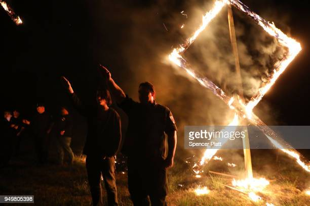 Members of the National Socialist Movement, one of the largest neo-Nazi groups in the US, hold a swastika burning after a rally on April 21, 2018 in...