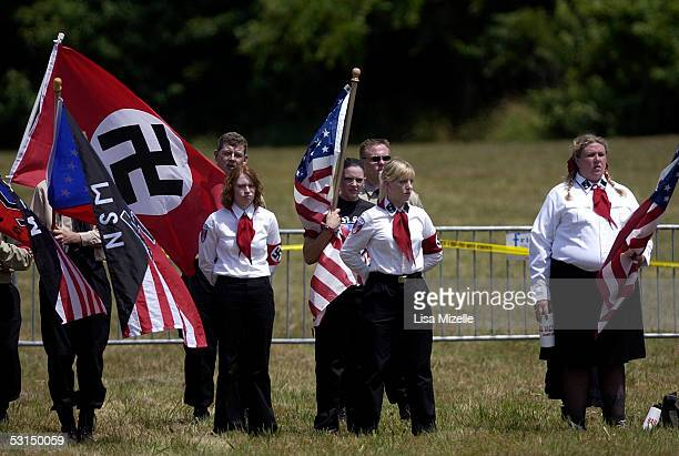 Members of the National Socialist Movement stand at attention while holding flags at a rally held at the Yorktown Battlefield June 25 2005 in...