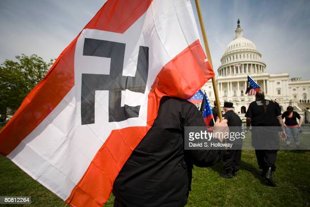 Members of the National Socialist Movement wave American Flags and NSM flags as they march from the Washington Monument to the grounds of the United...