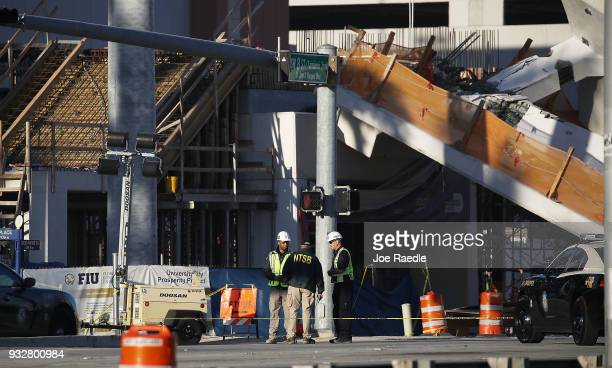 Members of the National Transportation Safety Board investigate the scene where a pedestrian bridge collapsed a few days after it was built over...