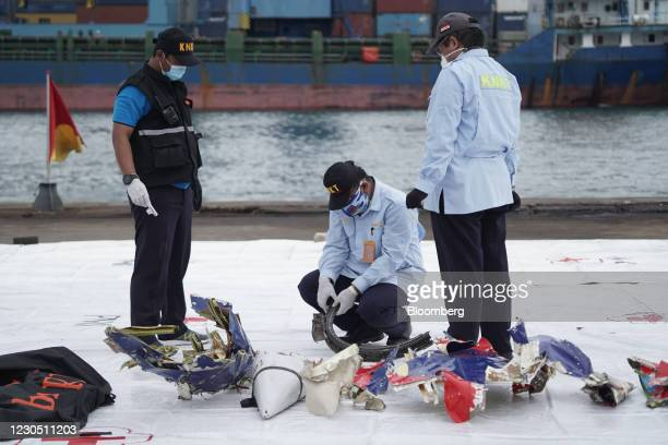 Members of the National Transportation Safety Committee examine debris recovered from the Sriwijaya Air SJ 182 crash site on the dockside at Tanjung...