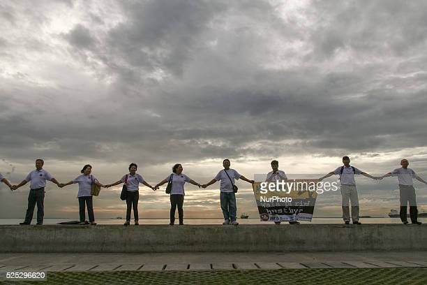 Members of the National Union of Journalist in the Philippines hold hands at the Baywalk in Manila to make a human chain in remembrance of the media...