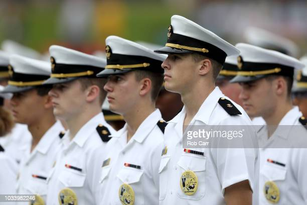 Members of the Navy Midshipmen look on during the playing of the national anthem before the start of the Navy and Lehigh Mountain Hawks game at...