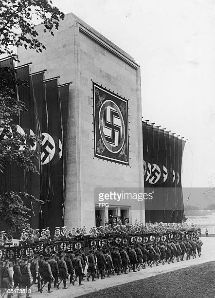 Members of the Nazi Sturmabteilung marching past the Luitpoldhalle with their banners at the Nuremberg Rally to mark the 8th Nazi Party Congress, 9th...