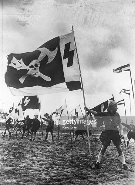 Members of the Nazi Youth Group from the age of six upwards take part in a flag display at an open air camp near Berlin