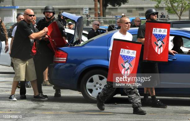 Members of the neonazi group The American National Socialist Movement group use shields to shelter from rocks and bottles thrown by an angry crowd of...