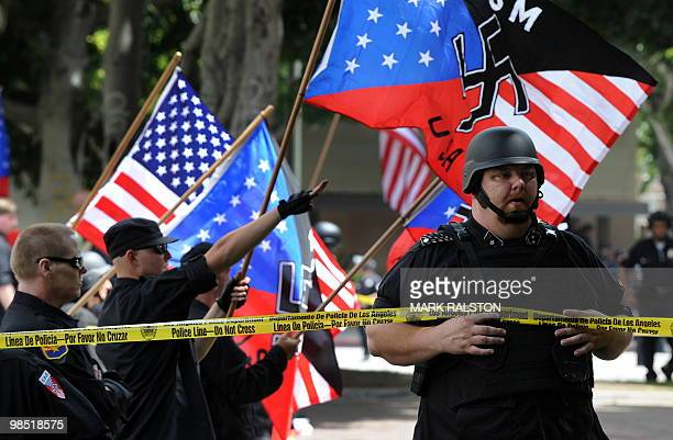 Members of the NeoNazi group The American National Socialist Movement watch an angry crowd of counterprotesters as the group held a rally in front of...