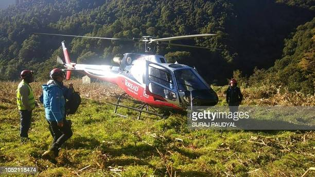 Members of the Nepali rescue team stand near an helicopter during the rescue operations for the bodies of nine climbers killed at Mount Gurja in the...