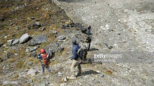Members of the Nepali rescue team walk along a mountainside during the rescue operations for the bodies of nine climbers killed at Mount Gurja in the...