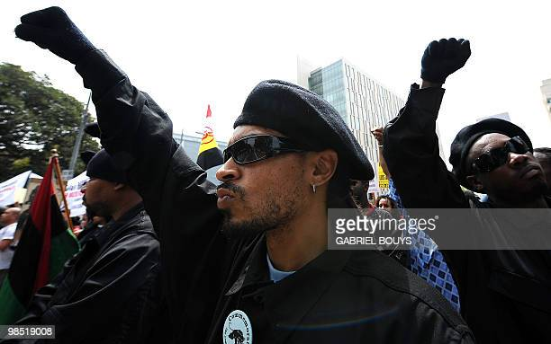 Members of the New Black Panthers group raise their arms during a demonstration of counterprotesters after the neonazi group The American National...